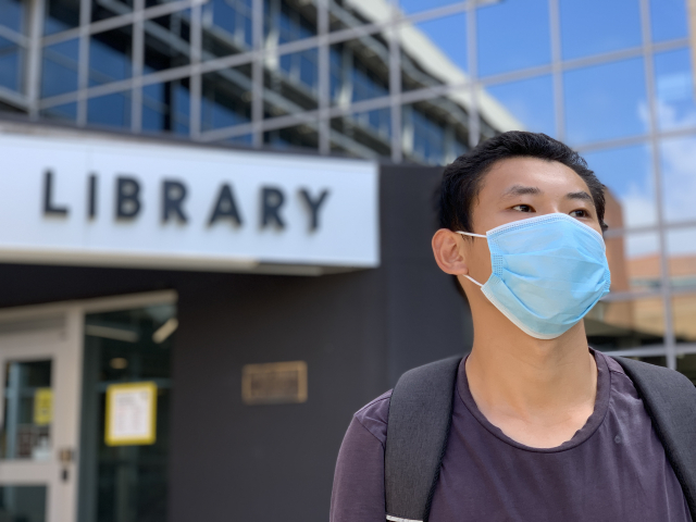 Masked student outside EWFM Library