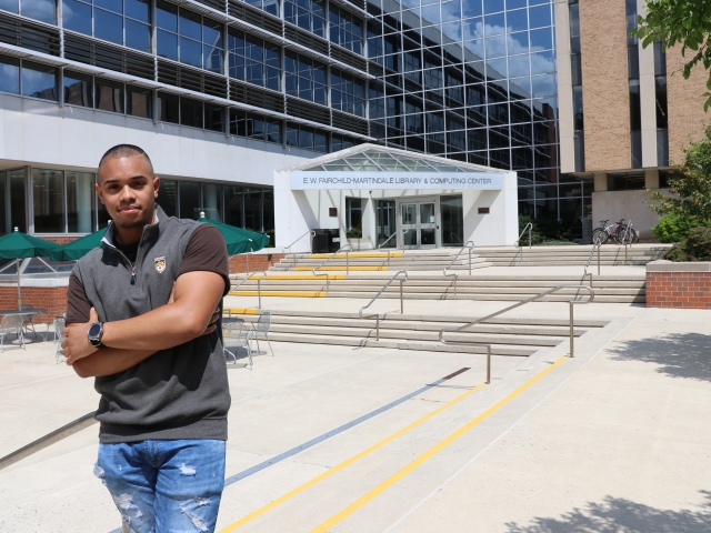 photo of student emplyee Victor Contreras outside the ewfm library