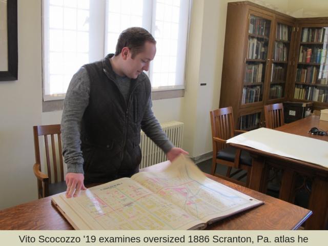 Vito Scocozzo examines oversized 1886 Scranton, Pa. atlas