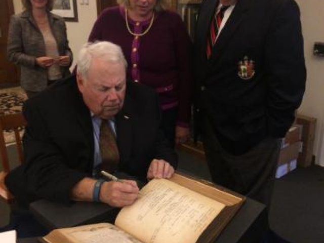 Captain John R. Linderman '59, '95P, updates entries in the bible, while Laura Linderman Barker '95 and John R. Linderman, Jr., look on. Lois Fischer Black, Curator of Special Collections observes the signing. Image appears courtesy of Emily Linderman '19.