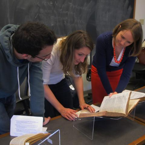 photo of jenna lay reviewing books with students in class