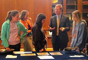 Michael Suarez and Jenna Lay review special collections documents with students in the Bayer Galleria